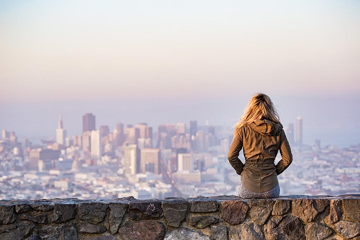 Nurse sitting on ledge contemplating summer travel assignment